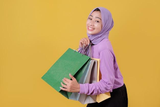 Sorridente ragazza carina felice utilizzando la carta di credito per sprecare soldi nel centro commerciale, tenendo le borse della spesa, comprare regali o regali, concediti la giornata
