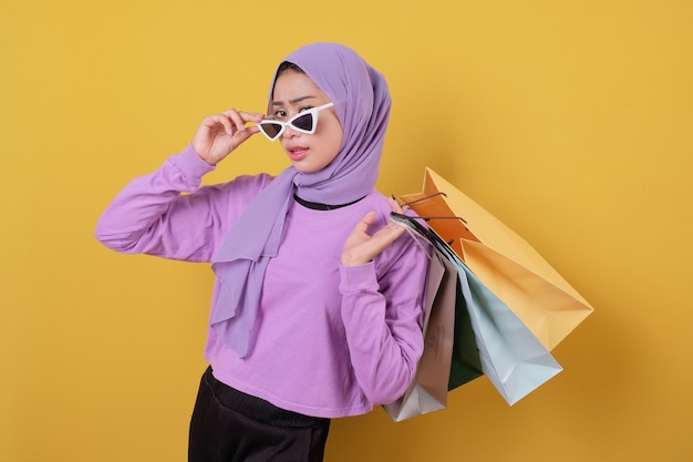 Sorridente bella ragazza felice utilizzando la carta di credito per sprecare soldi nel centro commerciale