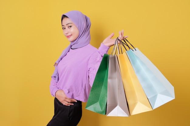 Sorridente ragazza carina felice a sprecare soldi nel centro commerciale, con in mano borse della spesa, comprare regali o regali, concedersi la giornata