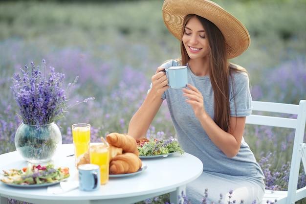 Sorridente donna felice che tiene tazza nel campo di lavanda