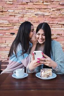 Donne felici sorridenti che si divertono e spettegolano, una sussurra all'orecchio della sua amica.