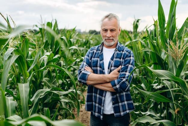 Sorridendo felice giovane agronomo o agricoltore che indossa la camicia a scacchi rossa prendendo e analizzando i campioni di terreno in una fattoria di mais