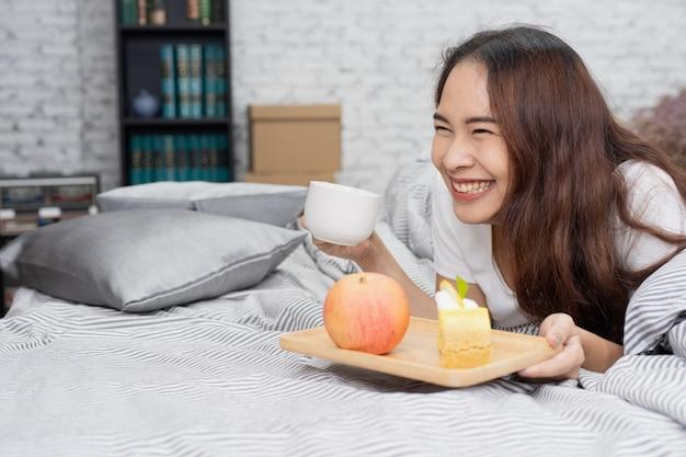 Donna in buona salute sorridente che mangia prima colazione con frutta e dolce sul letto