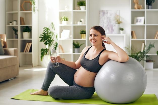 Sorridente giovane donna incinta in buona salute in abiti sportivi che si siede sulla stuoia di yoga e che si appoggia su fitball mentre beve l'acqua a casa
