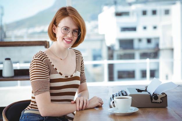 Donna sorridente dei pantaloni a vita bassa che si siede ad uno scrittorio con un caffè e una macchina da scrivere