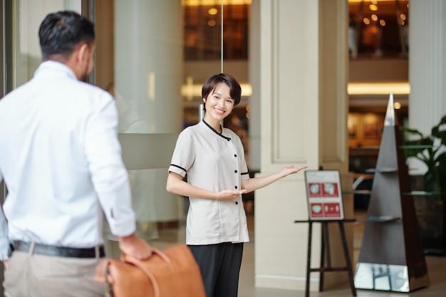 Sorridente e ospitale portiere che accoglie gli ospiti alle porte di un hotel di lusso