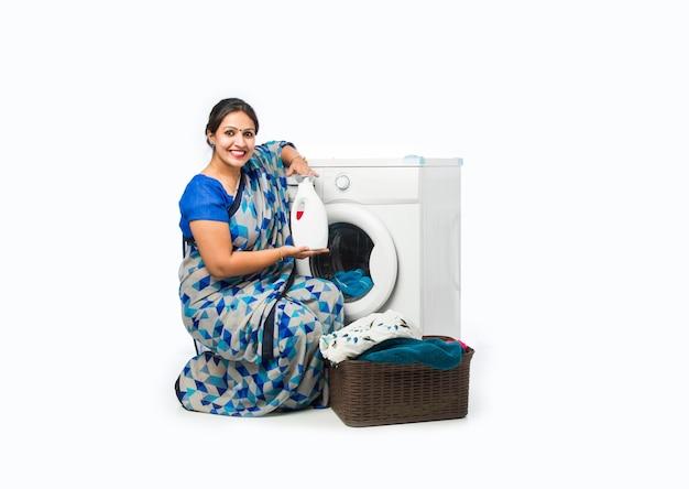 Sorridente casalinga asiatica indiana in saree in piedi vicino alla lavatrice con cesto di vestiti