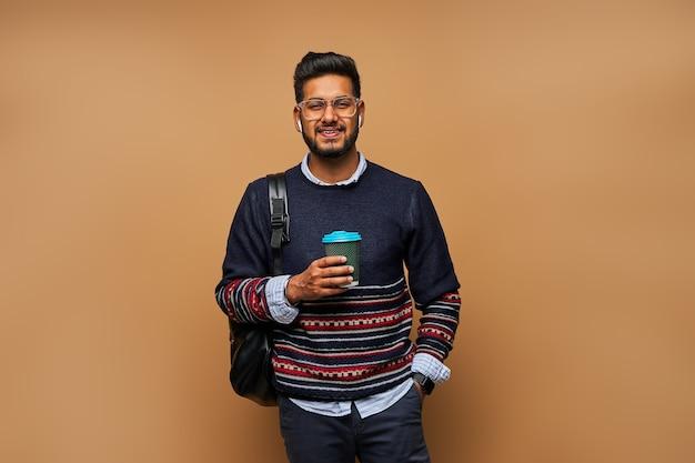 Studente indiano sorridente in bicchieri con zaino e caffè per andare sul muro.