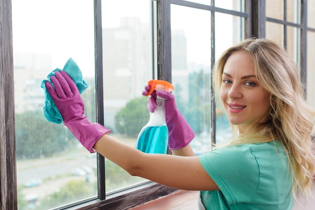 Bidello sorridente che pulisce finestra di vetro con il panno che esamina macchina fotografica Foto Premium
