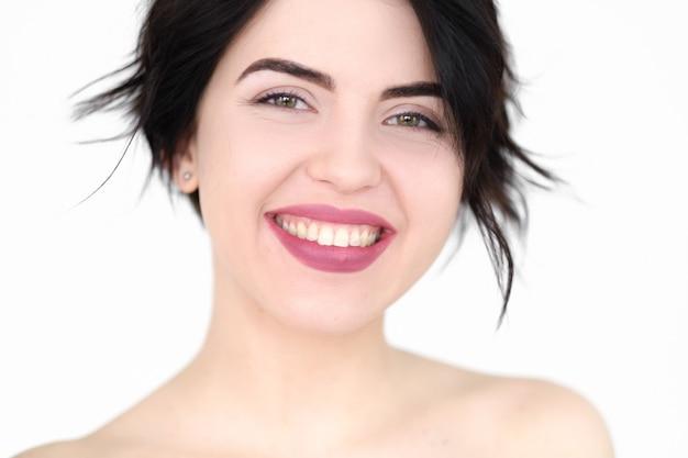 Sorridente gioiosa donna felice sul muro bianco.