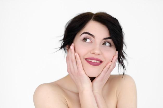 Sorridente donna allegra tenendo la testa tra le mani sul muro bianco.
