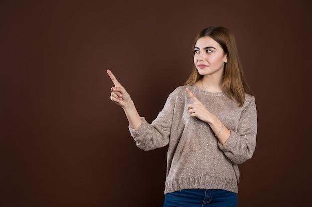 Donna allegra sorridente in maglione sciolto che posa contro la parete marrone dello studio che indica allo spazio della copia per la pubblicità o il testo promozionale. emozioni positive, sentimenti, gioia, felicità