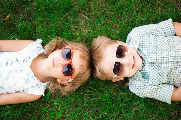 Bambini sorridenti in giardino in occhiali da sole