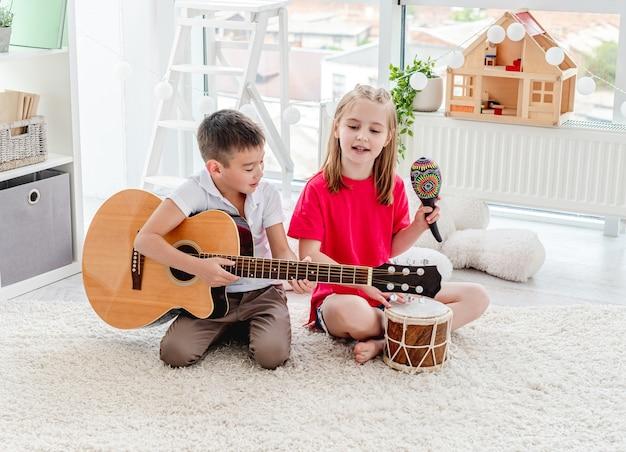 Bambini sorridenti che giocano su tamburo e chitarra in appartamento moderno