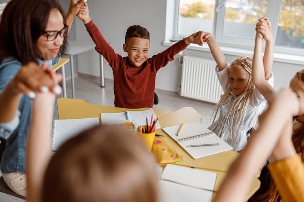Bambini sorridenti seduti al tavolo e alzando le mani