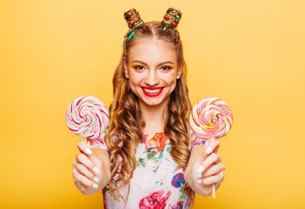 Signora sorridente che tiene due enormi lecca-lecca colorati