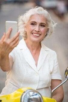 La signora sorridente esamina il telefono.