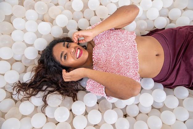 Sorridente ragazza latina sta mentendo uno strato di palline di plastica, sorride e felice pubblicità foto concetto di felicità