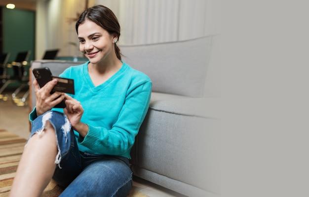 Il cliente sorridente della signora latina tiene la carta di credito del telefono cellulare fa shopping online