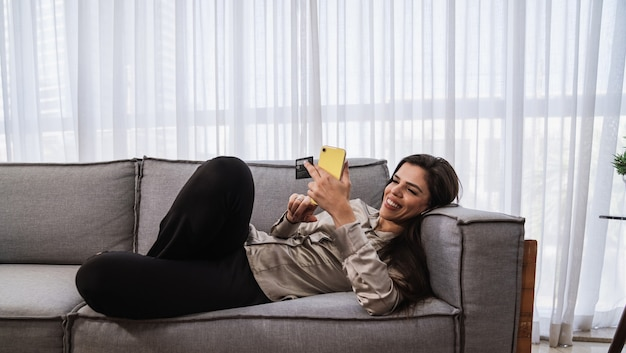 La signora latina sorridente tiene la carta bancaria di credito del telefono cellulare fa shopping online e fornisce il pagamento su internet