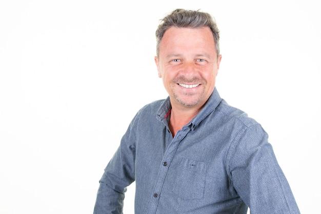 Giovane uomo barbuto di risata sorridente nella posa blu della camicia isolato sulla parete bianca