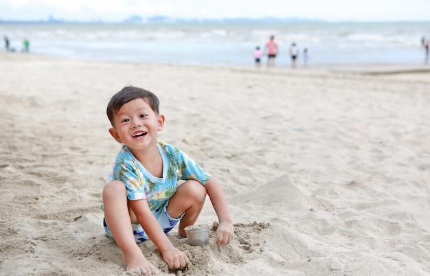 Il piccolo neonato asiatico sorridente si diverte a scavare la sabbia in spiaggia.