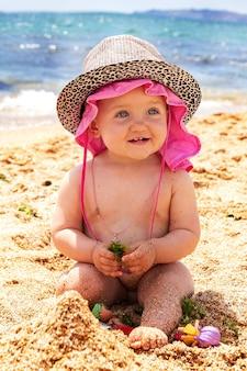 La piccola bambina sorridente sta giocando sulla spiaggia nella sabbia con i giocattoli il bambino sta prendendo il sole al sole