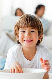 Ragazzino sorridente che mangia i chip che si trovano sul pavimento