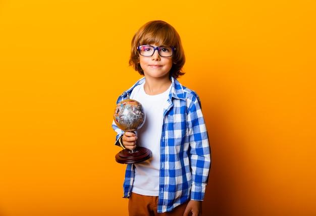 Sorridente ragazzino con gli occhiali 7 anni, con in mano un globo su sfondo giallo, ritratto in studio di un bambino. concetto di educazione