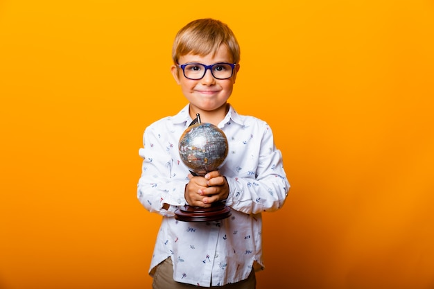 Sorridente ragazzino con gli occhiali, con in mano un globo su uno sfondo giallo, ritratto in studio di un bambino.