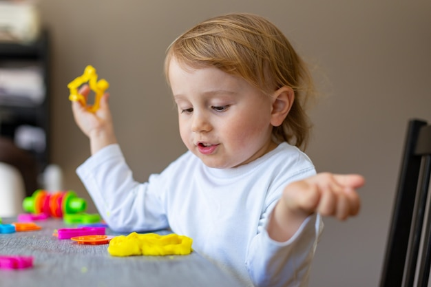 Stampi sorridenti del ragazzino dalla plastilina colorata sul tavolo