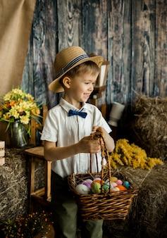Il ragazzino sorridente con una camicia, un farfallino e un cappello di paglia sta con un cesto di uova colorate nelle decorazioni di pasqua