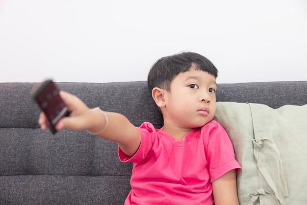 Il ragazzino sorridente guarda la tv e preme il telecomando sul comodo divano in soggiorno