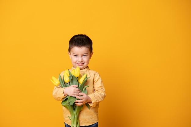 Ragazzino sorridente su sfondo giallo studio. allegro bambino felice con bouquet di fiori di tulipani.