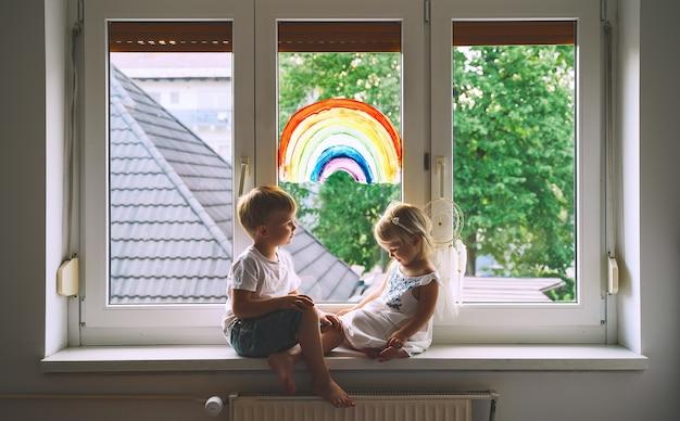 Bambini sorridenti sullo sfondo di un arcobaleno dipinto sulla finestra