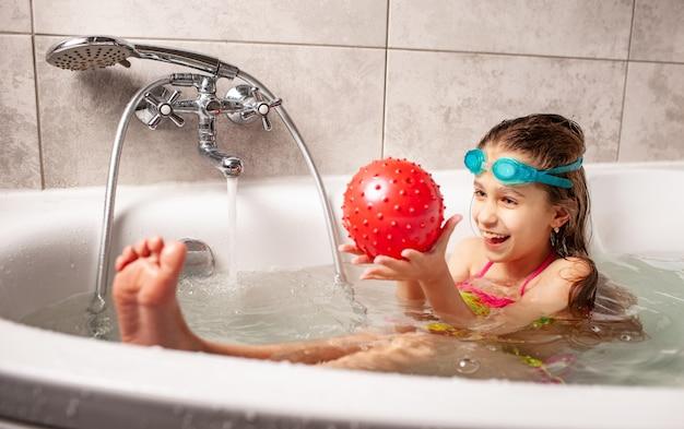 Sorridente bambina divertente in costume da bagno si diverte a giocare la palla mentre si fa il bagno nella vasca da bagno