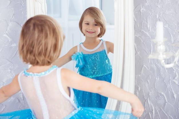 Bambina sorridente in vestito blu che osserva specchio messa a fuoco selettiva