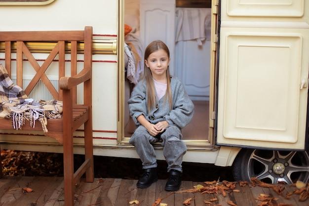 Sorridente bambina in abiti casual seduta sul portico camper camper rimorchio in giardino camping