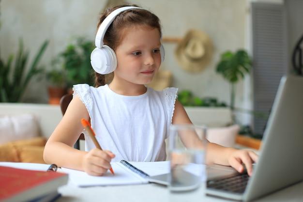 Bambina sorridente in cuffie che scrive a mano studia online utilizzando il laptop a casa, un bambino piccolo e felice carino con gli auricolari prende lezioni o lezioni su internet su pc.