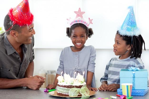 Bambina sorridente e la sua famiglia festeggia il suo compleanno
