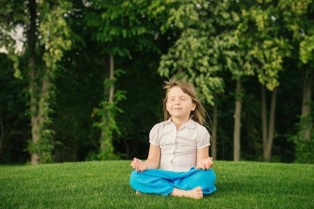 Bambina sorridente nella posizione di loto
