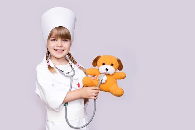 Bambina sorridente che gioca medico e orsacchiotto d'ascolto con lo stetoscopio isolato su bianco