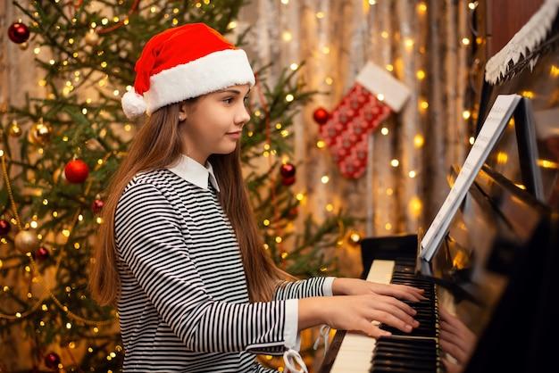 Bambina sorridente in cappello rosso della santa che gioca bella canzone sul pianoforte