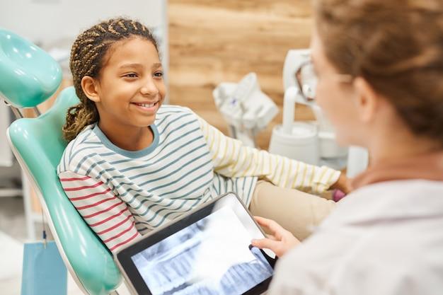 Bambina sorridente che si siede sulla poltrona odontoiatrica e ascoltando la raccomandazione del medico presso la clinica