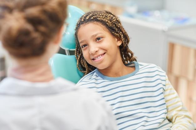 Bambina sorridente che si siede sulla poltrona odontoiatrica e parlando con il medico in ospedale