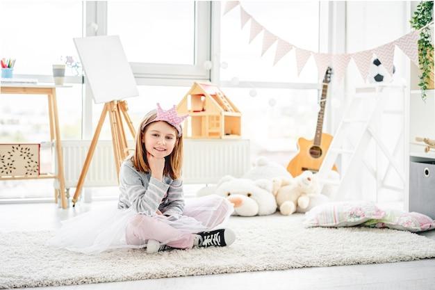 Bambina sorridente che si siede sul pavimento nella sala giochi carina