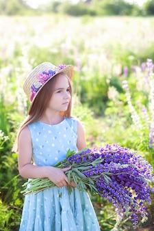 Bambina sorridente in un cappello di paglia e con un grande mazzo di lupini.