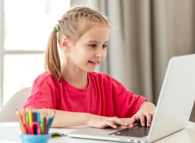 Bambina sorridente che parla in linea facendo uso della web cam del computer portatile