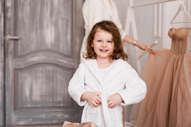 Bambina sorridente in un accappatoio bianco dopo un interno accogliente bagno bianco