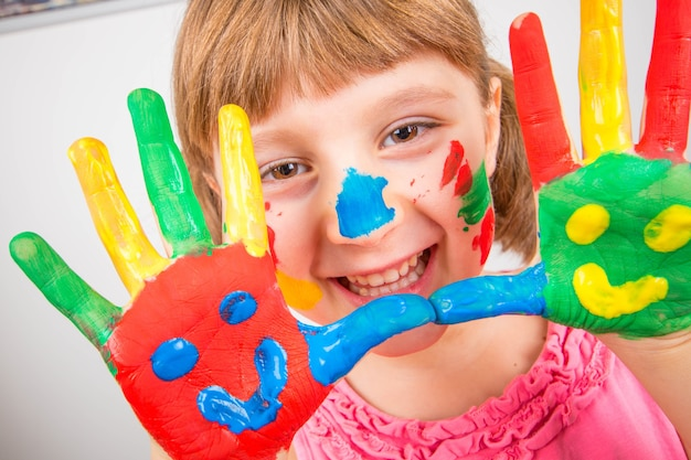 Bambina sorridente con le mani dipinte con vernici colorate
